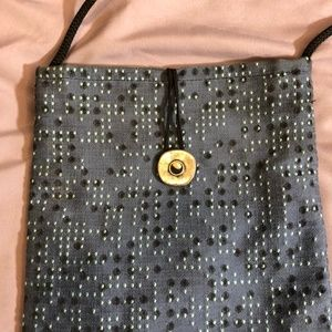 Small grey purse with raised design and dots.